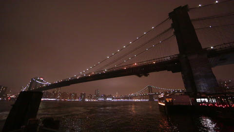 Shot at night overlooking the East River and the Brooklyn Bridge as a boat crusi Footage