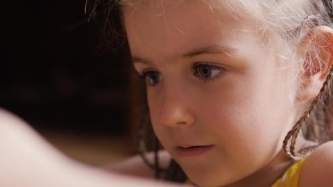 Cute child girl face portrait watch cartoons via smart phone Footage