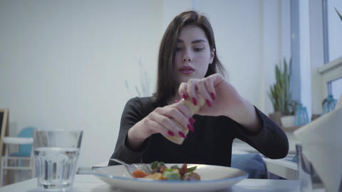 Portrait of young pretty girl with red manicure salt her delicious appetite dish Live Action