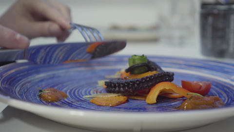 Woman eating beautifully served appetite octopus and grilled fresh vegetables on Live Action