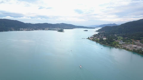 Aerial view of a big lake in mountains. Boat moves on the lake. Klagenfurt Footage