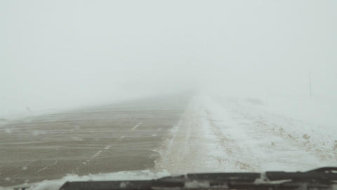 Snowstorm on the road. The wind covered road with snow Footage