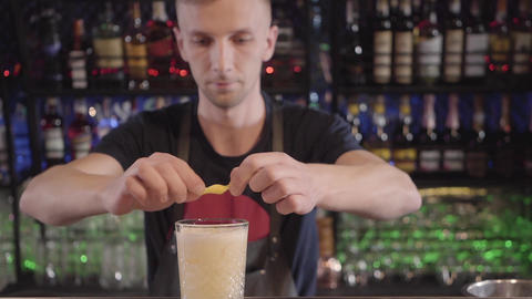 Bartender in restaurant at the bar making delicious cocktail and serving glass Footage