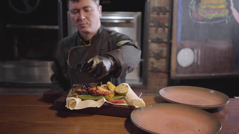 Profession chef of restaurant in special black uniform serves plate of salmon Live Action