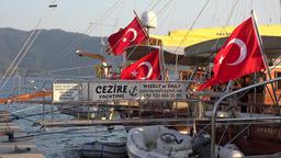 Turkey Aegean coast Mugla Marmaris yacht gangways and national flags in evening Footage