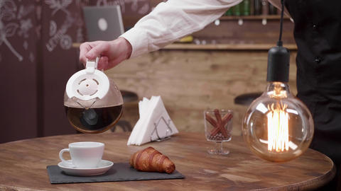 Slowly pouring a cup of fresh dark coffee in a white cup Live Action