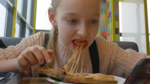 Portrait teenager girl eating cheesy pizza with salami in italian fast food cafe Footage