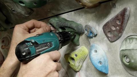 man screws handhold Live Action