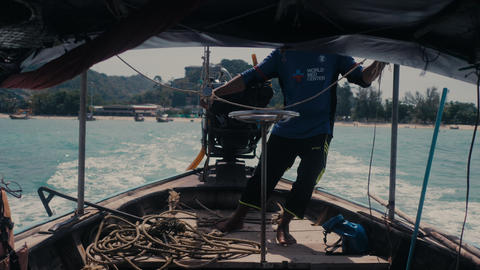 Unrecognizable man drives a long-tail thai boat with outboard motor 4K Live Action