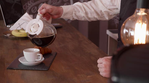 Man hand pour coffee from a pitcher on a bar counter Footage