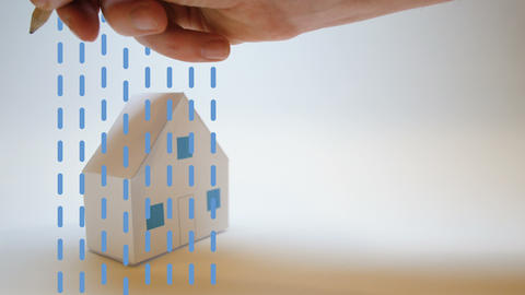 an insurer's hand protects a paper house from natural disasters Footage