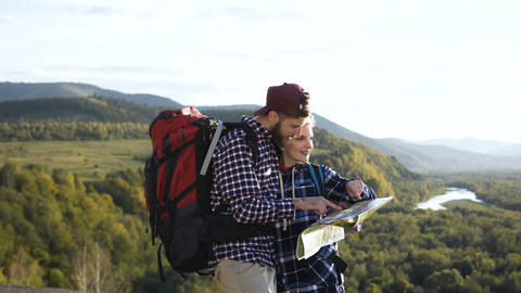Portrait shot of young man and woman with map in the mountains Live Action