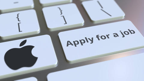 APPLE INC company logo and Apply for a job text on the keys of the computer Footage
