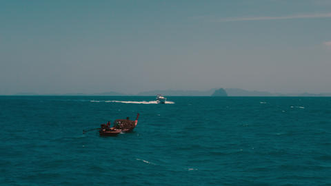 view of small fishing boat and modern speedboat floating in the sea in 4K Footage
