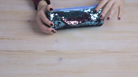 Female hands holding a brown and blue pencil box Footage
