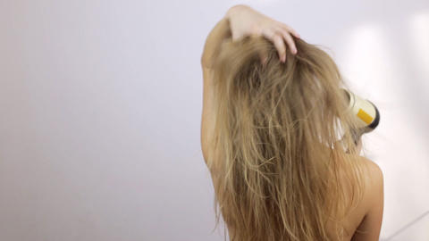 The girl the blonde dries wet hair with the hair dryer Footage
