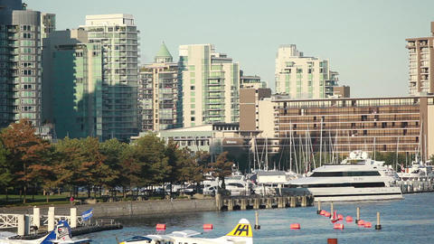 Panning zoomed shot of the Olympic Village down to the water where planes are do Footage