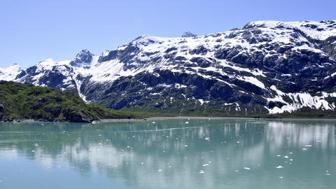 Traveling view of snow covered mountains and small ice glaciers floating in Glac Footage