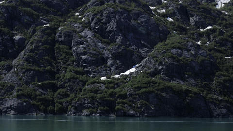 Traveling time-lapse of the snowy and rocky shore of Glacier Bay, Alaska Footage
