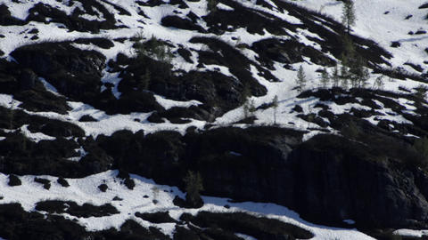 Zoomed in traveling view of the side of a snow covered mountain in Alaska Footage