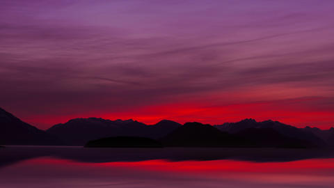 Silhouette of mountain range with purple and red sky in Alaska Footage