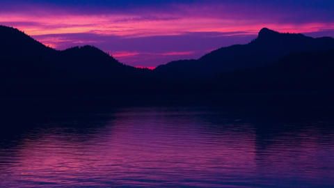 Time lapse of a pink sunset behind the silhouette of mountain ridge in the Insid Footage