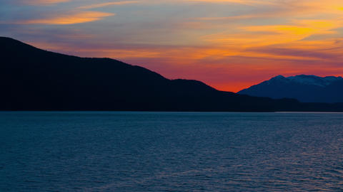 Traveling time-lapse of a silhouetted sunset from a cruise ship near Haines, Ala Footage