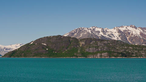 Time lapse view of green, rocky, snow capped mountains surrounded by glassy blue Footage