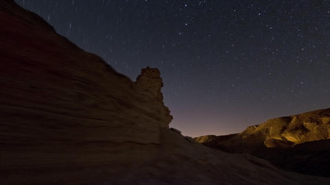 Tracking footage of desert rock formation, and cosmos moving in the sky above Footage