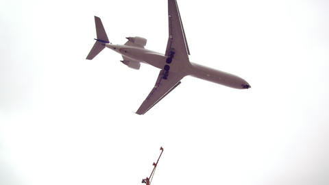 Shot of overhead plane turning and flying over traffic. Footage