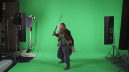 Front shot of a warrior with a sword and ax, shot in slow motion against a green Footage