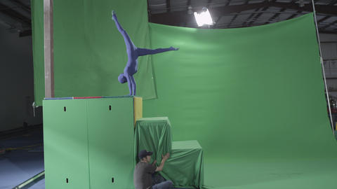 Slow motion green screen shot of woman mimicking a ninja climbing a structure Footage