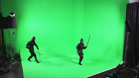 Static shot of two people dressed as ninjas posing in front of the camera Footage