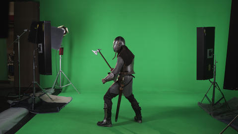 Side shot of man in chain mail holding an ax in hand. shot in slow motion agains Footage