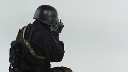 Back shot of a soldier pointing an assault rifle. Shot in slow motion against gr Footage