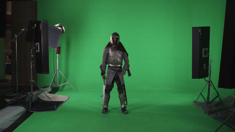 Shot of man in armour with a sword in right hand. Shot in slow motion against a  Footage
