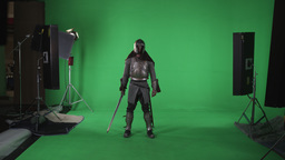 Shot of man in armor raising sword from side to across his chest. Slow motion ag Footage
