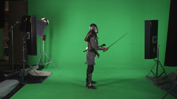 Side shot of knight raising sword from side to shoulder. Slow motion against gre Footage