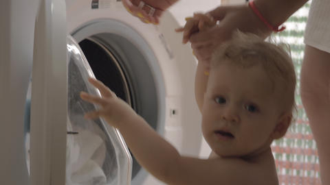 Curious baby girl is looking at mother doing household chores Footage