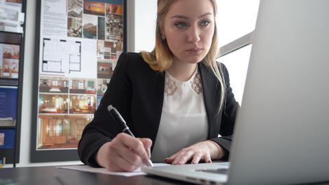 Woman entrepreneur writing with pen business document on table in modern office Footage