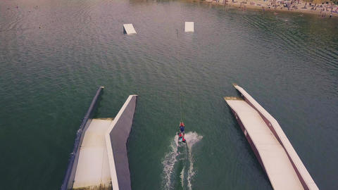 Flying over girl wakeboarding in wake park Footage