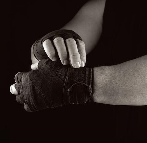 man wraps his hands in black textile bandage for sports Photo