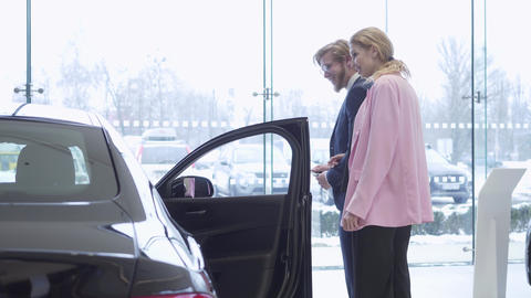 Happy couple chooses a new vehicle in a car dealership. Car showroom Footage
