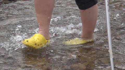 Trekker traveller overcomes a water barrier Live Action