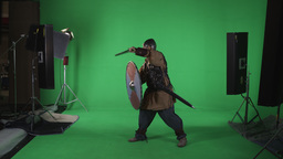 Side shot of man in armor, hitting his large round shield with sword. Shot again Footage