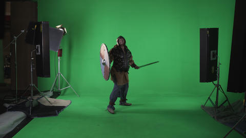 Shot of man with shield & sword as if in a battle gets hit and takes a knee. Footage