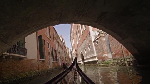 View from a gondola as it glides under a bridge in canal Footage