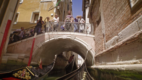 Gondola glides past other gondola's through and under a bridge Footage