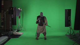 Shot of man dressed as a warrior turned away from camera with sword in hand. Aga Footage