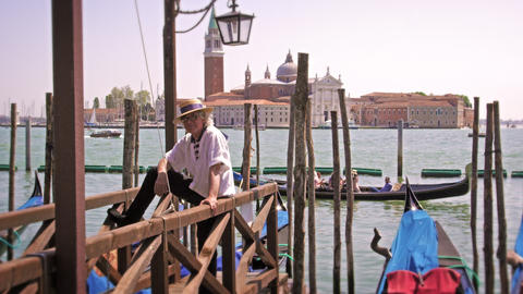 VENICE - MAY 2: A Gondolier waits on a dock on the Grand Canal on May 2, 2012 in Footage